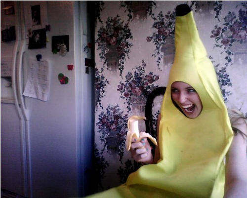 Girl dressed as a banana is eating a banana and making a really strange face.