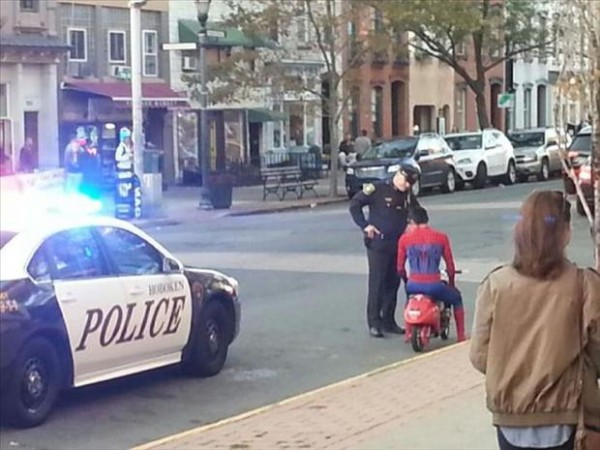 Spider-Man on tiny motorcycle is pulled over by city police.